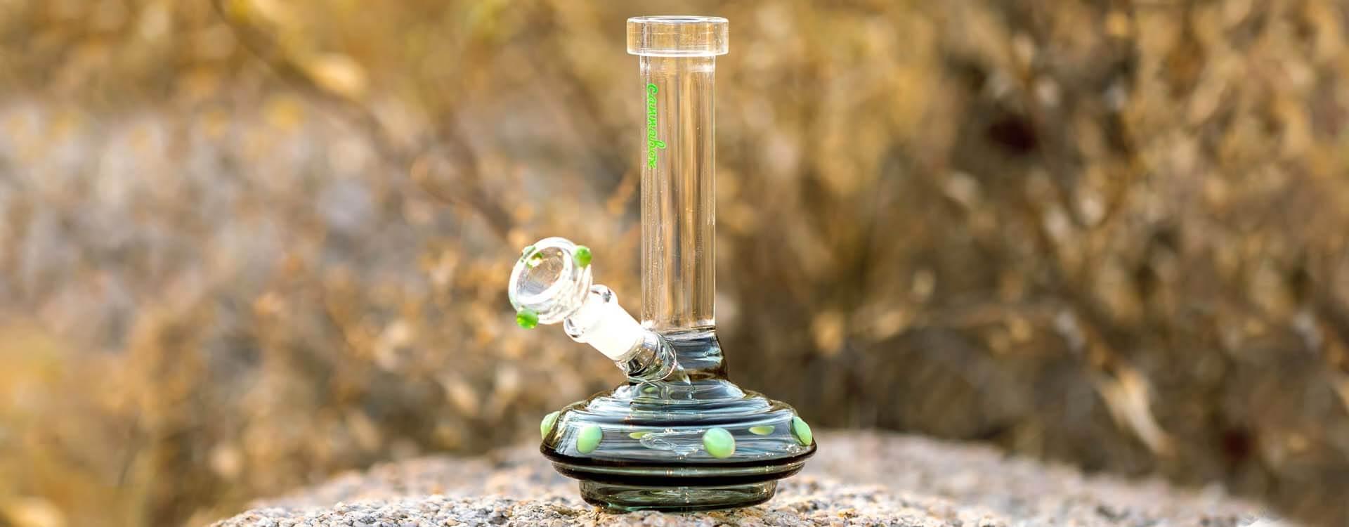 Sklenené mini bongo položené na kameni v prírode